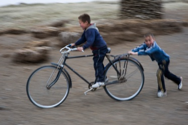 nomadic boys play with a old bike