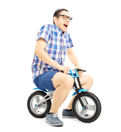 Excited young male riding a small bicycle
